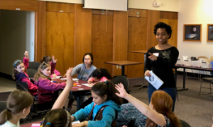Outreach co-chair Destenie Nock helps Brownie Girl Scouts earn their Inventor Badge.