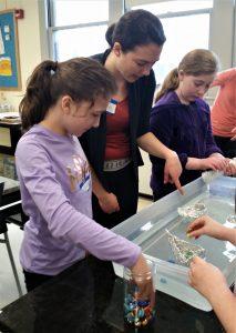 "A GWIS volunteer helps Junior Girl Scouts test ""cargo boat"" designs."