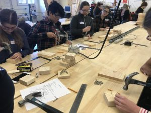 Cadette Girl Scouts learn woodworking skills like hammering.