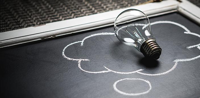 Lightbulb in a thought cloud on a chalkboard