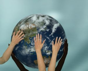 hands representing diversity, touching earth globe