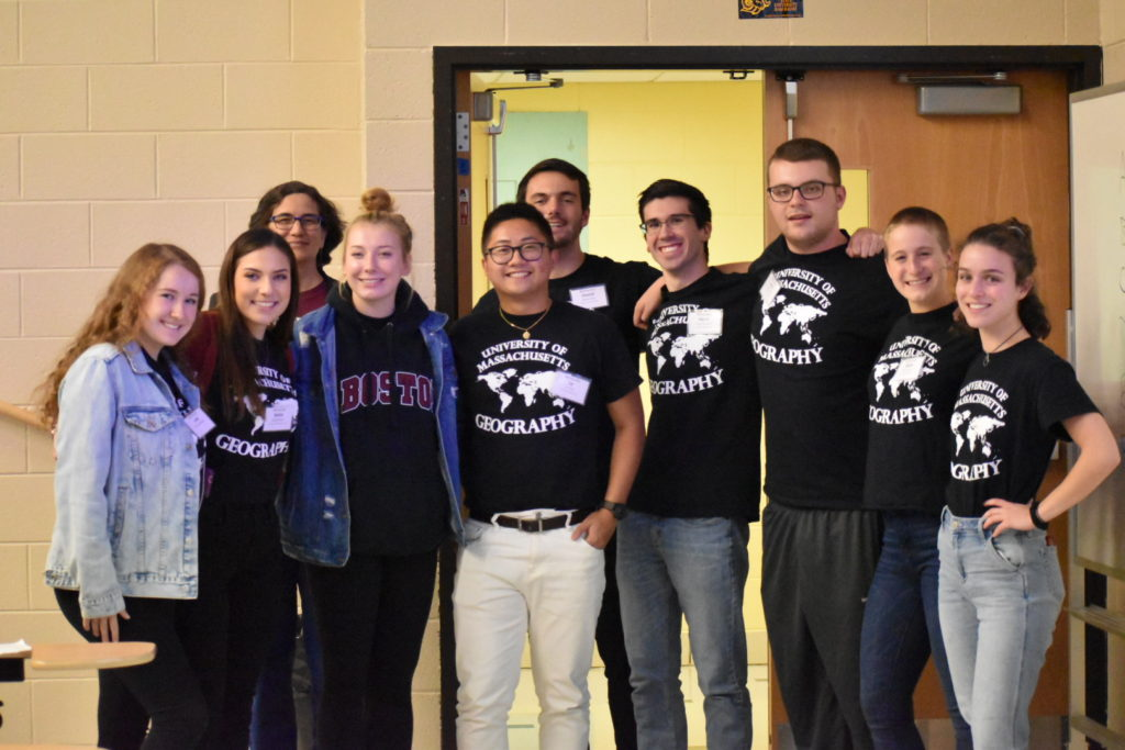 From left to right, Julia Schiemann, Kelsie Butler, Dr. Eve Vogel, Ellen Fay, Le Tran, Dan Finn, Harry Chernin, Mark Doherty, Molly Autery, and Izzy Mezzina gather for a group photo at NESTVAL wearing matching black and white UMass Geography shirts!