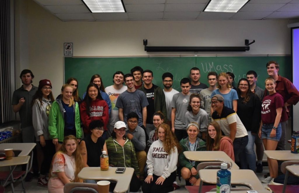 About thirty smiling students gather for a group photo in front of a chalkboard.