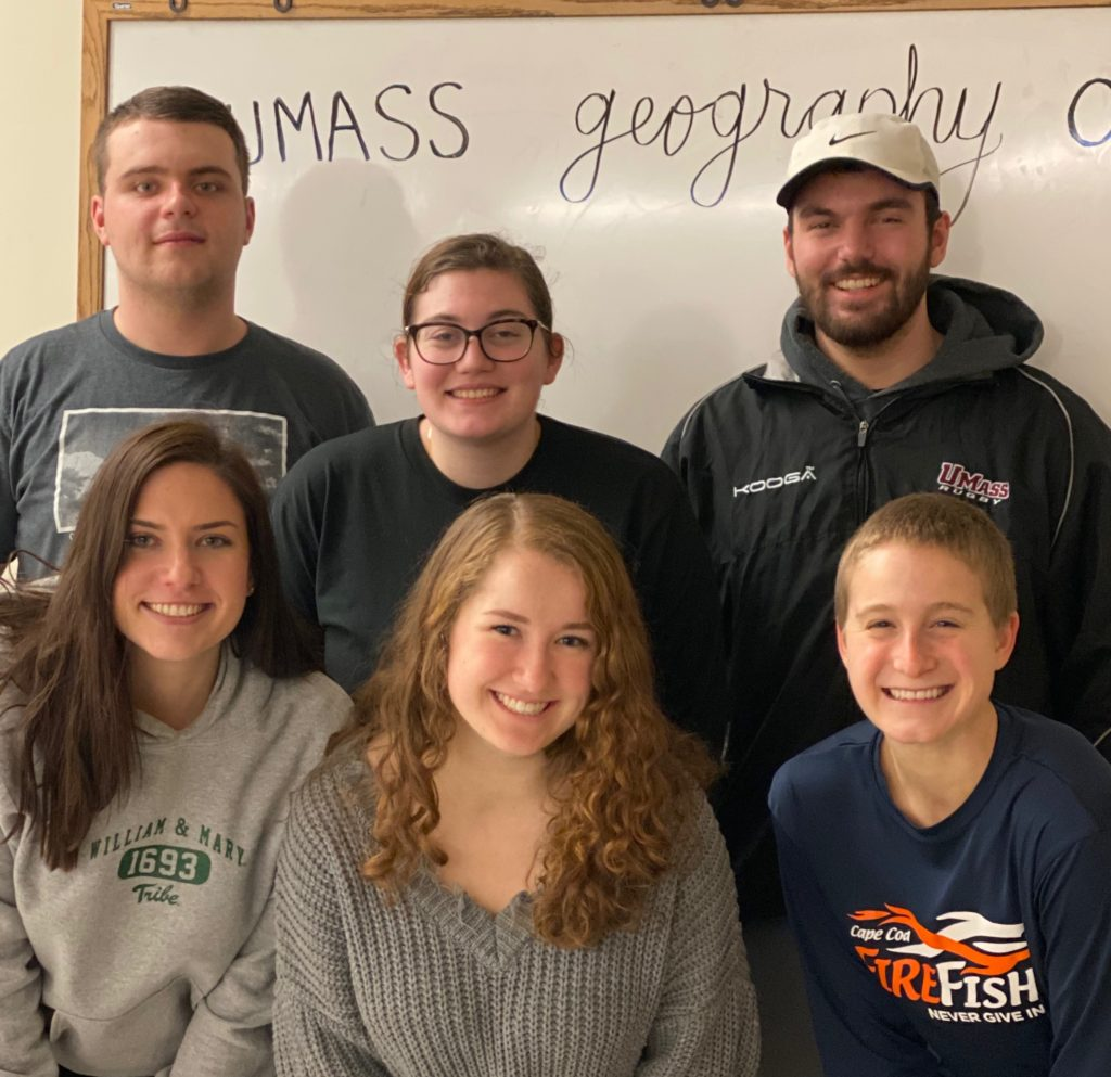 The six Geography Club E-Board representatives pose in two rows in front of a white board at their first meeting of the semester.